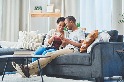 Buy stock photo Shot of a young couple sharing a moment together sitting on the couch in their apartment while she enjoys a cup of coffee