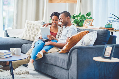 Buy stock photo Shot of a smiling young loving couple browsing on a tablet together while she has her legs across his waist sitting on the couch in their apartment