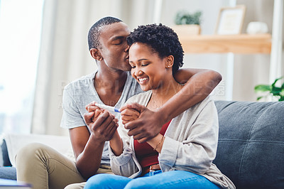 Buy stock photo Cropped shot of a young couple embracing, kissing and holding hands as she holds a positive pregnancy test while sitting on the couch in their apartment