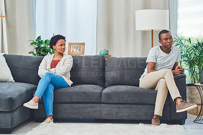 Buy stock photo Shot of a young couple sitting apart on a couch after an argument while she looks at him in disdain