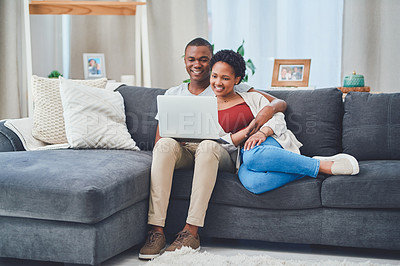 Buy stock photo Shot of a smiling young loving couple browsing on a laptop together while sitting on the couch in their apartment
