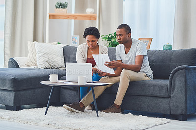 Buy stock photo Shot of a young couple sitting together on a couch in their apartment while reviewing budgets on a laptop and papers together