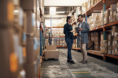 Buy stock photo Shot of a young man and woman using a digital tablet while working together in a warehouse