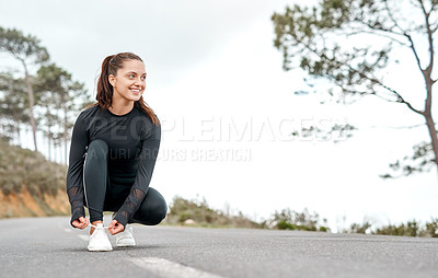 Buy stock photo Full length shot of an attractive young woman tying her shoelaces before exercising outdoors alone