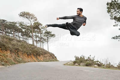 Buy stock photo Full length shot of a handsome young man doing a flying kick during his workout outdoors