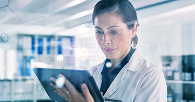 Buy stock photo Shot of a young woman using a digital tablet while going through notes on a glass screen in a lab