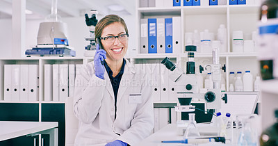 Buy stock photo Portrait of a young woman talking on a cellphone in a lab