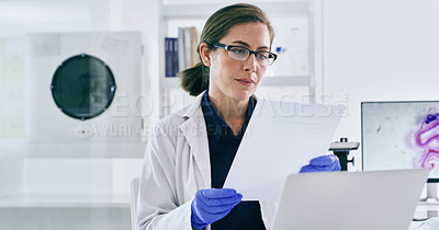 Buy stock photo Shot of a young woman going through paperwork while working on a laptop in a lab