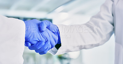 Buy stock photo Closeup shot of two unrecognisable scientists shaking hands in a lab