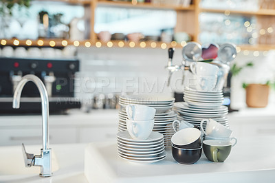 Buy stock photo Shot of a pile of dishes next to a sink in a cafe