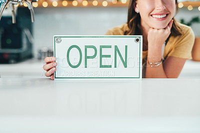Buy stock photo Cropped shot of a woman holding up an open sign in her cafe
