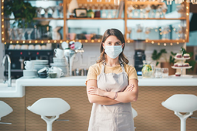Buy stock photo Portrait of a confident young woman wearing a face mask while working in a cafe