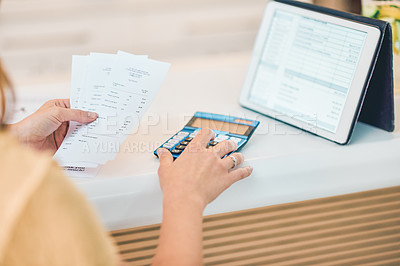 Buy stock photo Shot of a woman using a digital tablet and calculator while going through paperwork in a cafe