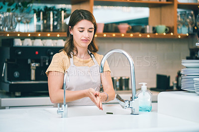 Buy stock photo Shot of a young woman washing her hands while working in a cafe