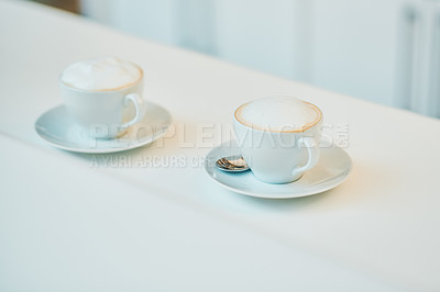 Buy stock photo Shot of two cups of coffee on a counter in a cafe