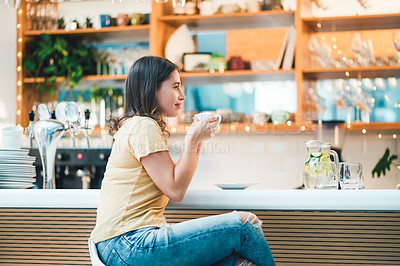 Buy stock photo Shot of a woman enjoying a cup of coffee while sitting in a cafe