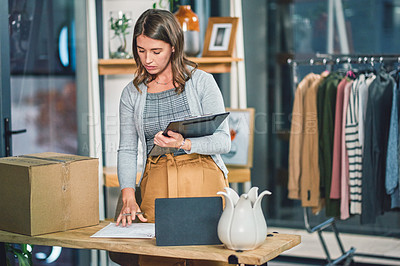 Buy stock photo Shot of a young woman organising deliveries in a boutique