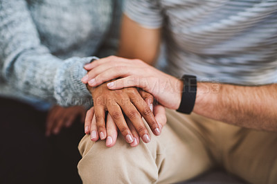 Buy stock photo Cropped shot of an unrecognizable couple sitting close together at home and holding hands