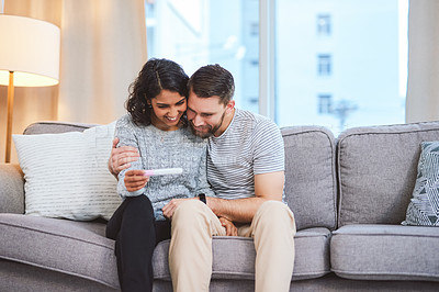 Buy stock photo Cropped shot of a happy young couple sitting on the sofa together and holding a positive pregnancy test