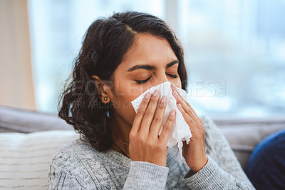 Buy stock photo Cropped shot of an attractive young woman sitting on the sofa at home and feeling sick