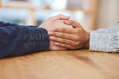 Buy stock photo Cropped shot of an unrecognizable couple sitting together at home and holding hands