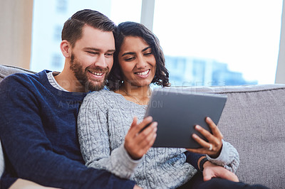 Buy stock photo Cropped shot of a happy young couple sitting together at home and using a tablet for a video chat