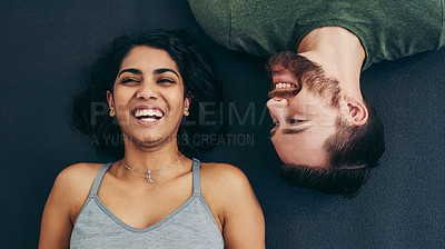 Buy stock photo High angle shot of a young couple lying on the floor at home