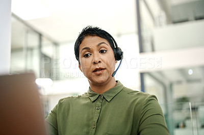 Buy stock photo Shot of a mature businesswoman wearing a headset while working on a laptop in an office
