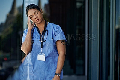 Buy stock photo Shot of a mature doctor looking stressed out while standing outside a hospital
