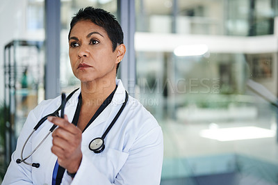Buy stock photo Shot of a mature doctor looking thoughtful in a hospital