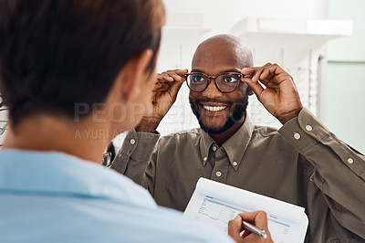 Buy stock photo Shot of a an optometrist helping a young man choose a new pair of glasses