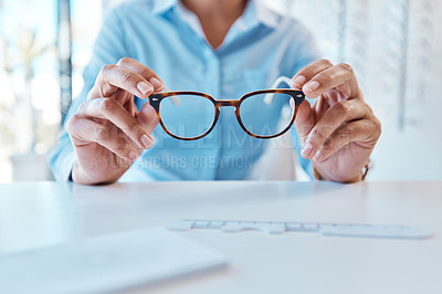 Buy stock photo Shot of a woman buying a new pair of glasses at an optometrist store