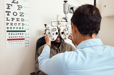 Buy stock photo Shot of an optometrist examining her patient's eyes with an optical refractor