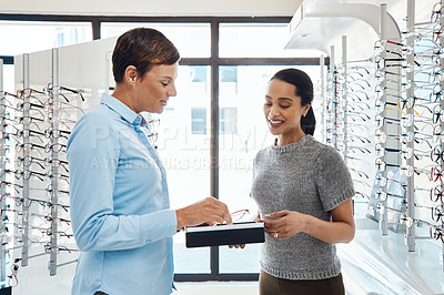 Buy stock photo Shot of a an optometrist helping a young woman choose a new pair of glasses