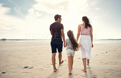 Buy stock photo Shot of a couple and their daughter out for a walk on the beach