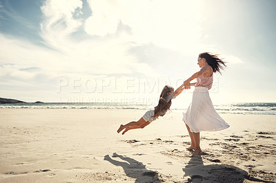 Buy stock photo Shot of a woman and her daughter being playful on the beach