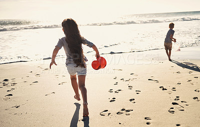 Buy stock photo Shot of a little girl and boy running towards the water with their beach buckets