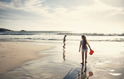 Buy stock photo Shot of two kids filling their buckets with water at the beach
