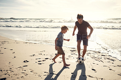 Buy stock photo Shot of a man and his young son playing soccer on the beach