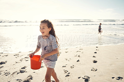 Buy stock photo Shot of a little girl carrying a bucket with water on the beach