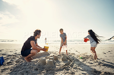 Buy stock photo Shot of a man building sandcastles on the beach with his two kids