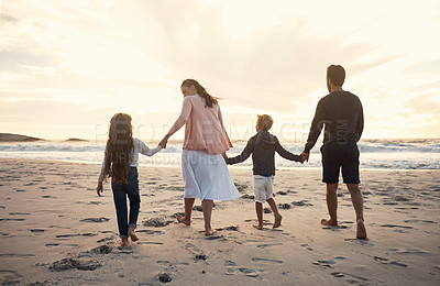 Buy stock photo Shot of a couple out for a stroll on the beach with their two kids