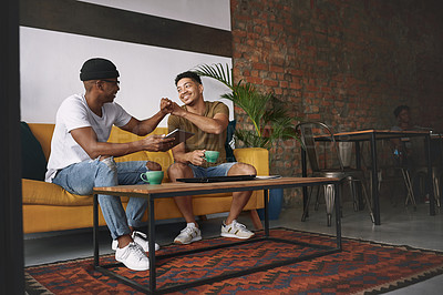 Buy stock photo Shot of two young men sharing a fist bump while sitting in a coffee shop