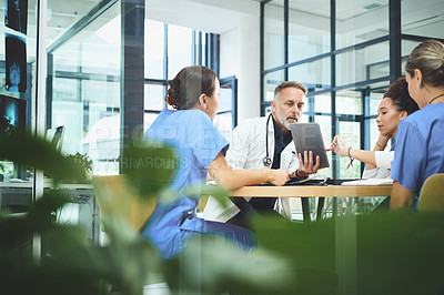 Buy stock photo Shot of a team of doctors using a digital tablet during a meeting in a hospital