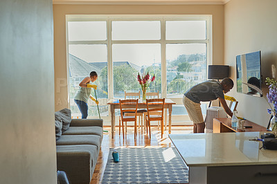 Buy stock photo Shot of a young couple cleaning the living room of their apartment