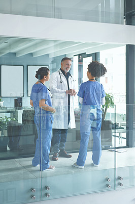 Buy stock photo Cropped shot of a handsome mature doctor standing with his nurses and having a discussion in the clinic
