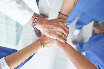 Buy stock photo Cropped shot of an unrecognizable group of healthcare professionals standing huddled together with their hands piled in the middle