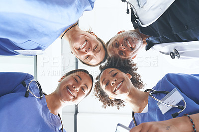Buy stock photo Low angle portrait of a diverse group of healthcare professionals standing huddled together with their heads together in the middle