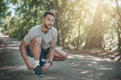 Buy stock photo Shot of a handsome young mean tying his running shoe laces