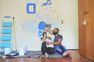Buy stock photo Shot of a couple sitting at home with their baby while busy painting a room